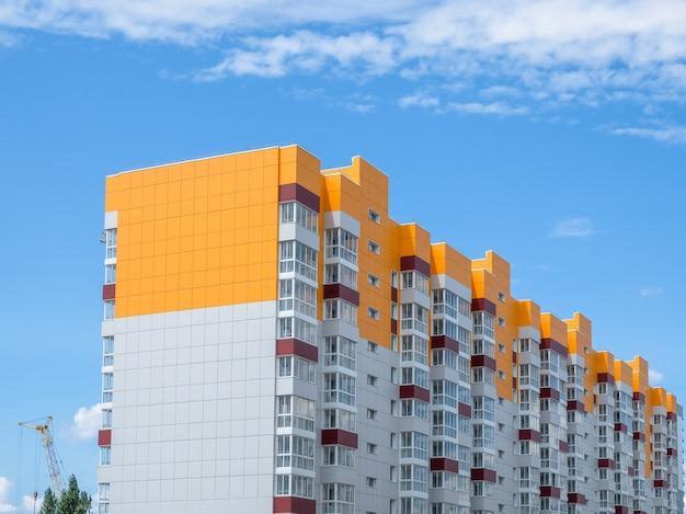 モダンで美しい新しい建物。青い空を背景に色付きの壁。スペースをコピーします。