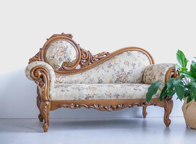 隅に花と白い背景の上のモダンな美しいソファ