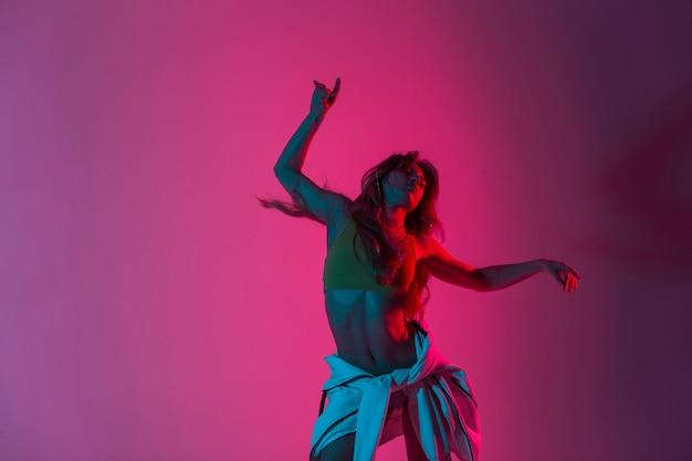 明るいネオンピンクの光でスタジオで踊るパーカーの靴のスタイリッシュなトップのモダンな美しい若い女性ダンサー。カラフルなキラキラとファッショナブルな女の子のファッションモデルのダンス
