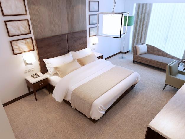 흰색과 짙은 갈색의 대비와 침대 뒤의 나무 벽 장식이있는 조명이 포함 된 일광이있는 현대적인 침실입니다.