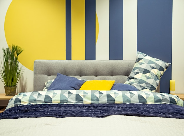 Modern bedroom interior in blue and yellow tones.