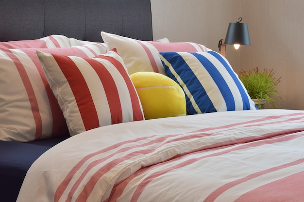 Modern bedroom interior with colorful pillows and reading lamp on bedside table