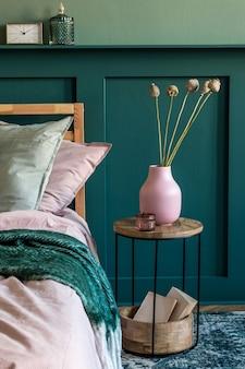 Современный интерьер спальни с дизайнерским журнальным столиком, цветами в вазе и элегантными личными аксессуарами. красивые простыни, одеяло и подушки. . стильная домашняя постановка. обшивка стен. подробности