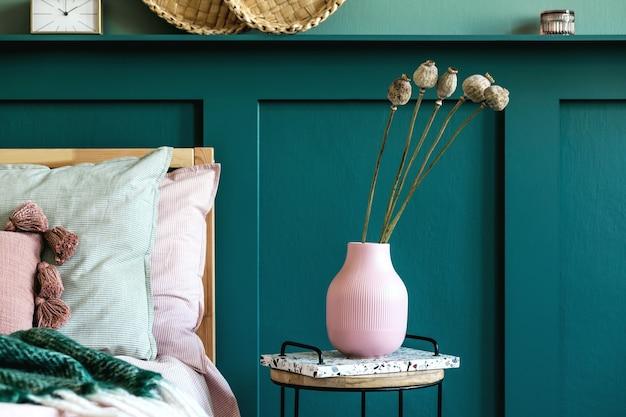Современный интерьер спальни с дизайнерским журнальным столиком, цветами в вазе и элегантными личными аксессуарами. красивые простыни, одеяло и подушки. шаблон. стильная домашняя постановка. обшивка стен. подробности