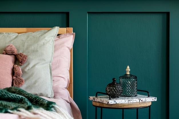 Современный интерьер спальни с дизайнерским журнальным столиком, стеклянными коробками и элегантными личными аксессуарами. красивые простыни, одеяло и подушки. . стильная домашняя постановка. обшивка стен. подробности