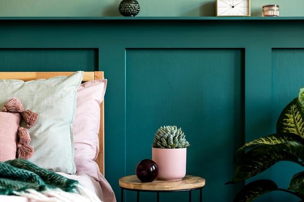 Современный интерьер спальни с дизайнерским журнальным столиком, сочными, растениями и элегантными личными аксессуарами. красивые простыни, одеяло и подушки. . стильная домашняя постановка. обшивка стен. подробности