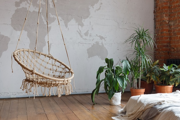Modern bedroom interior with green houseplants and a swing