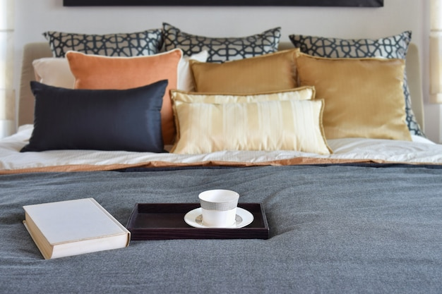 Modern bedroom interior with teacup on decorative wooden tray and white book on the bed