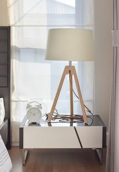 Современный интерьер спальни с деревянной лампой и будильником на тумбочке