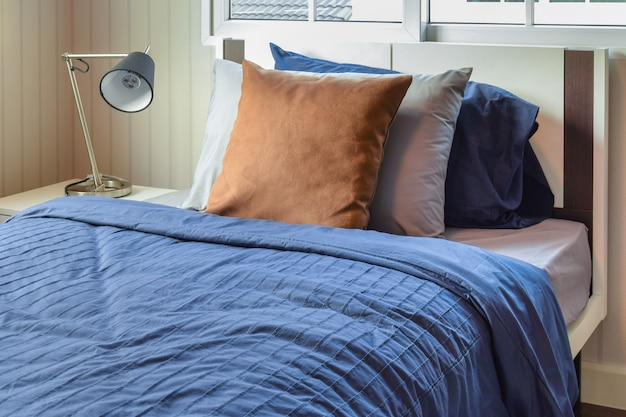 Modern bedroom with brown pillows on blue bed