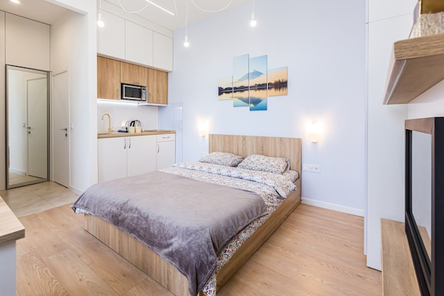 크고 세련된 침대와 작은 주방이있는 현대적인 침실