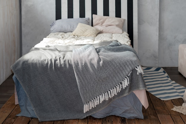간단한 가구, 회색 침구 및 목재 침대 머리판을 갖춘 현대적인 침실.