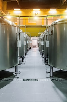 현대 맥주 공장. 맥주 저장 및 발효를위한 강철 탱크 열. 햇빛 효과
