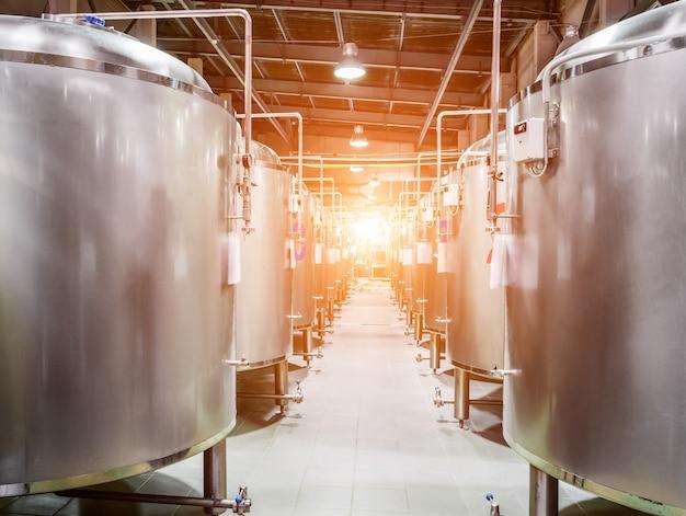 현대 맥주 공장. 맥주 발효 및 저장용 강철 탱크. 햇빛 효과