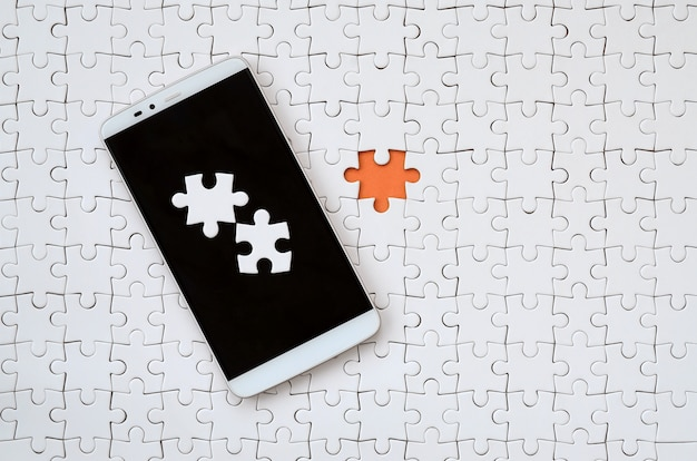 A modern big smartphone with several puzzle elements on the touch screen lies on white jigsaw puzzle