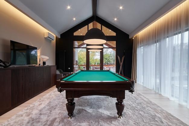 Современная бильярдная с красивым столом и большими окнами.