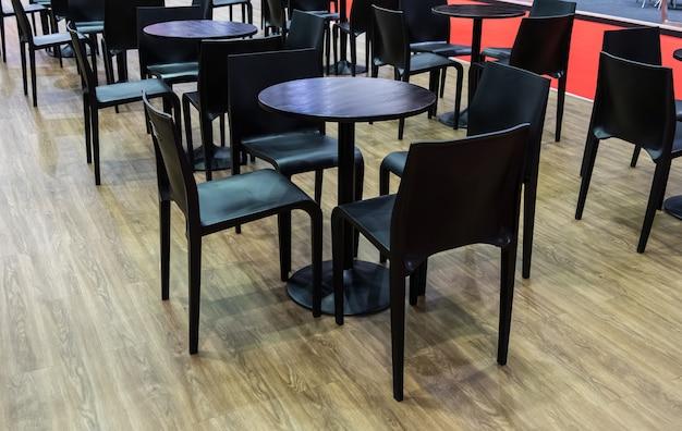 Современный черный стул и круглый деревянный стол