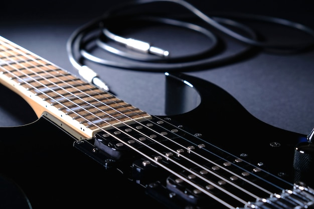 Modern black electric guitar with jack cable
