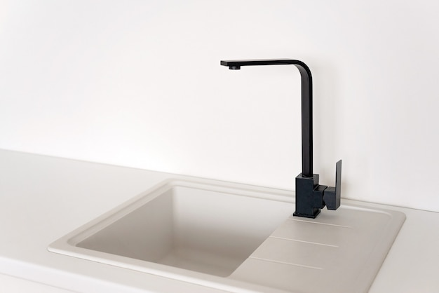 Modern black faucet in a white kitchen sink. soft selective focus.