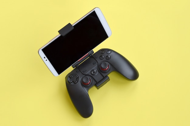 Modern black gamepad for smartphone on yellow background. mobile video gaming device