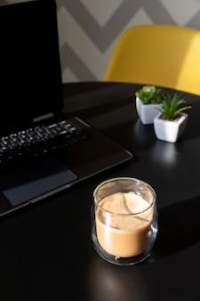 ラップトップ、一杯のコーヒーと植物とモダンな黒いキッチンテーブル