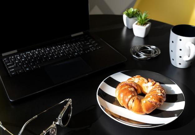 ノートパソコン、一杯のコーヒー、レディースアクセサリーとモダンな黒いキッチンテーブル