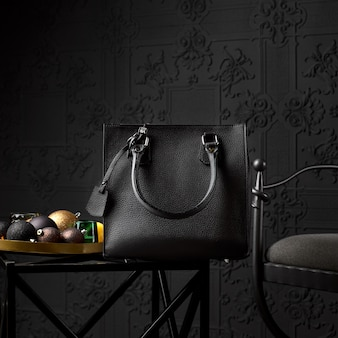 Современная черная кожаная сумка для деловой женщины на журнальном столике.