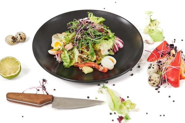 Современная черная тарелка с аппетитным овощным салатом