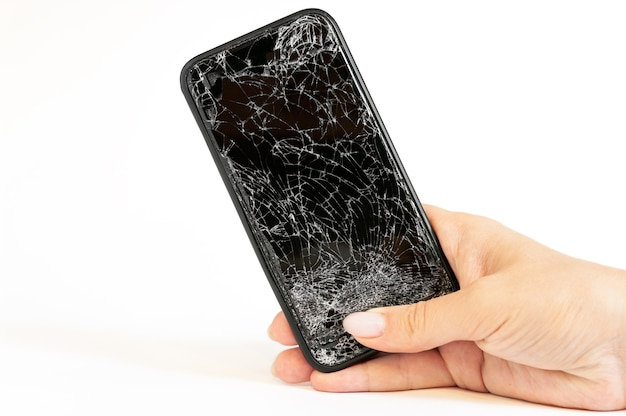 Modern black smartphone with highly broken screen in women hand on white wall