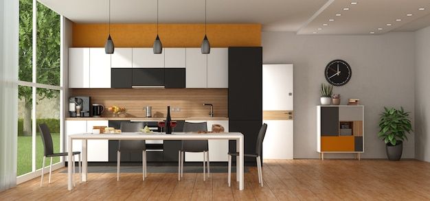 Modern black and white kitchen against an orange wall, with dining table