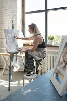 スツールに足を保持し、パレットを使用してキャンバスに絵を描く眼鏡の現代のブロンドの髪の芸術家
