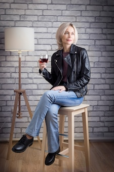 Modern blond mature woman sitting on bar stool drinking wine and thinking about her new idea.