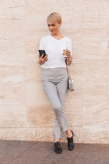 Modern blond woman with short hair using cell phone, while standing against beige wall outdoor in summer with takeaway coffee