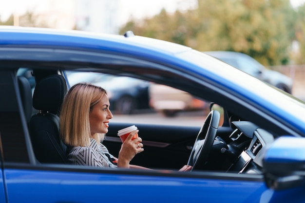 市内で運転中にコーヒーを飲みながらモダンなブロンドの女性