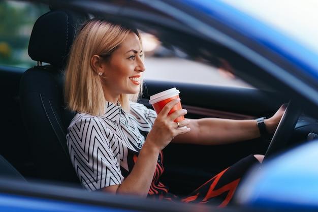 Donna bionda moderna che mangia un caffè per andare mentre si guida in città