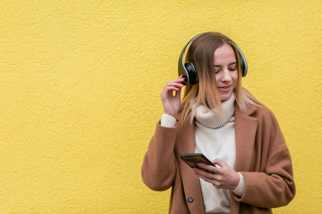 Modern blonde woman listening to music on headphones with copy space