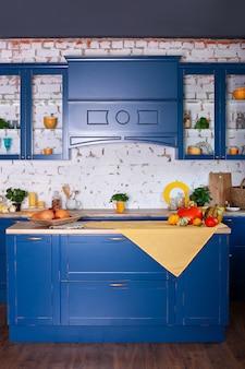 家具付きのロフトスタイルのモダンな青いキッチンインテリア。装飾が施されたスタイリッシュなスカンジナビア料理。素朴なスタイルの木製キッチン。空の木製テーブルとキッチンインテリアの黄色い春の装飾。