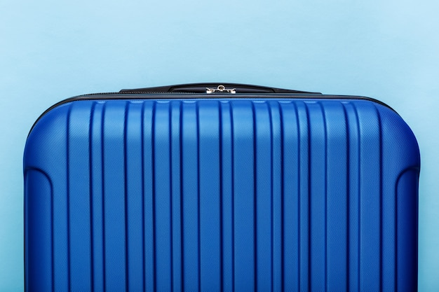 Modern blue suitcase on blue background close up with copy space for text. minimal style travel concept. vacation trip..