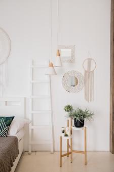 Современный бохо интерьер гостиной в уютной квартире. минималистичный скандинавский стиль, внутренняя лестница, растения, картины, корзина из ротанга и дизайнерские аксессуары. стильный домашний декор.