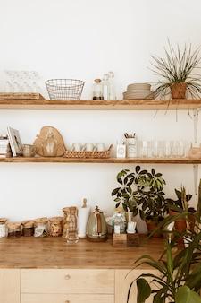 현대 boho 스타일 홈 주방 인테리어 개념. 나무 선반, 접시, 식기, 장식