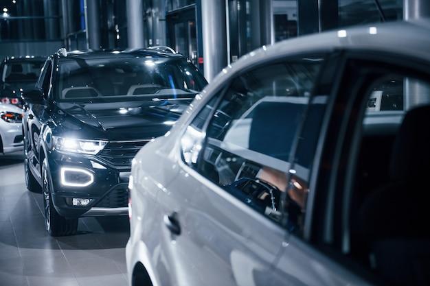 오토살롱에 현대적인 새로운 흑백 자동차가 주차되어 있습니다.