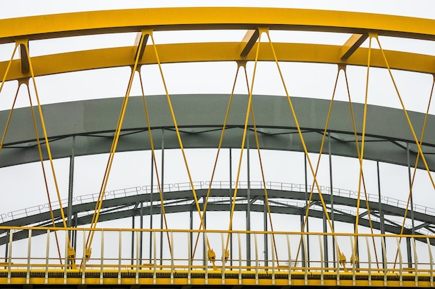 Modern bridge with yellow and grey metal fragments