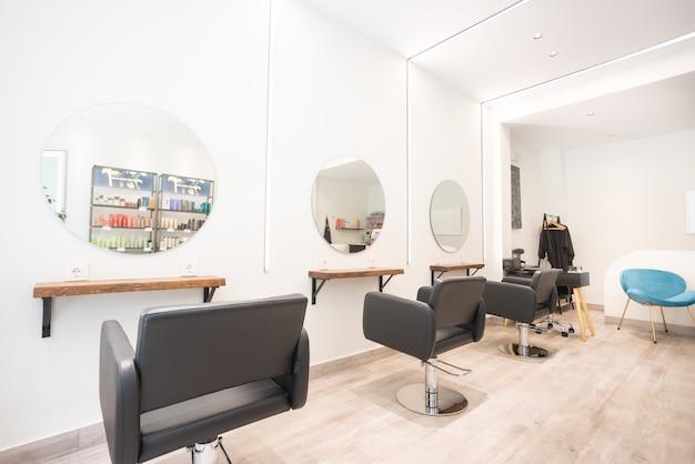 黒の椅子ラウンドミラーとネオンライトを備えたモダンな明るい美容院ヘアサロンインテリアビジネス