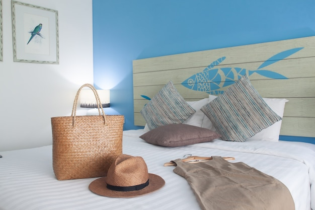 Modern bright bedroom with summer clothes, dress, hat and bag on white bed.