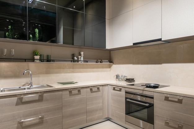 Современный, светлый, чистый интерьер кухни с техникой из нержавеющей стали в элитной квартире.