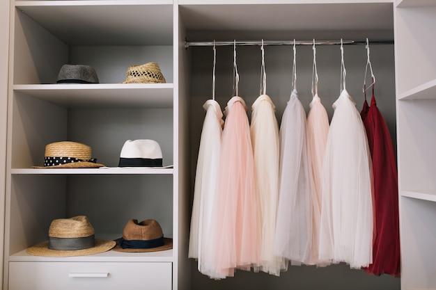Современная светлая гардеробная с полками. в гардеробе висят модные шляпы, красивые розовые и красные платья.