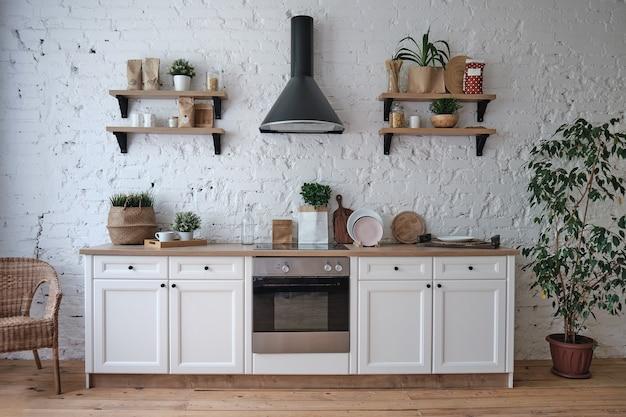 Современный яркий интерьер кухни с белыми стенами, мебельные полки для посуды