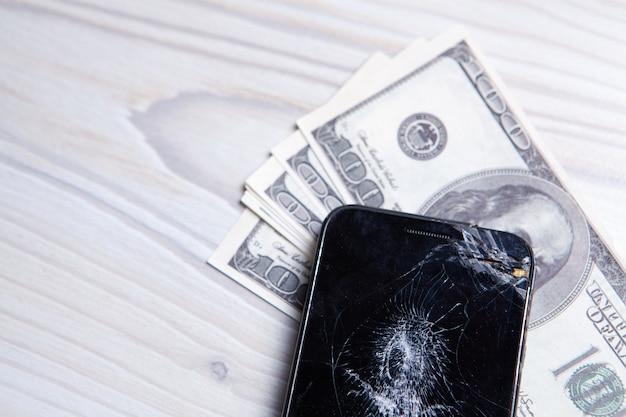 Современный сломанный мобильный телефон и доллары