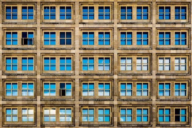 青いガラス窓とさびた美学を備えたモダンな茶色の建物