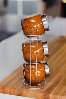Современный коричневый набор кухонных банок для специй, чая или кофе, вертикально стоящий на столе.